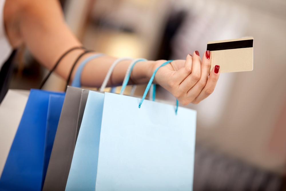 Woman shopping and paying with a debit or credit card